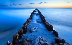 Old breakwater in North sea in dusk Stock Photos