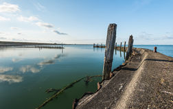 Old breakwater in a small harbor Stock Photos