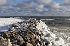 Old breakwater in winter. Stock Photos