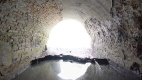 Old brick abandoned semicircular drainage tunnel that goes outside, timelapse