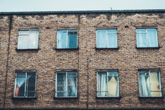 Old brick apartment block. With two rows of curtained windows and discoloration on the brickwork viewed from below Royalty Free Stock Photography