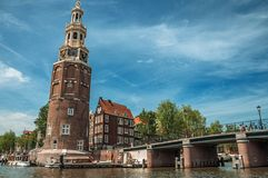 Old brick bell tower and bridge near the tree-lined canal with moored boats and blue sky in Amsterdam. Famous for its huge cultural activity, graceful canals Stock Images