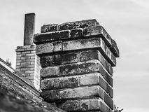 Old brick brick chimney on the house roof stock photography