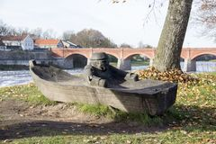Old Brick bridge across the River Venta in the city of Kuldiga Latvia and wooden fisherman in the boat figure on front. royalty free stock image