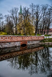 The old brick bridge, Latvia. Old red brick bridge of Kuldiga, Latvia. Street view with curch in the background. Bridge and trees reflecting in the water. No Royalty Free Stock Photography