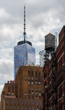 Old brick building in New York City with World Trade Center tower in background. Historic brick building with water tower on top in New York City, with World royalty free stock photography