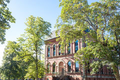 Old Brick Building Under Green Trees and Blue Sky Stock Images