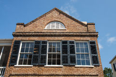 Three Windows with Black Shutters in Old Brick Stock Image