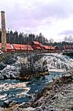Old brick buildings foundry. Nestled in a narrow valley along the river Lomma. The buildings straddle the river, with several pedestrian bridges connecting Stock Photo