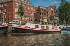 Old brick buildings near the tree-lined canal bank with moored boats and sunny blue sky in Amsterdam. Famous for its huge cultural activity, graceful canals Royalty Free Stock Photo