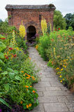 An old brick built arbour. An arbour in the grounds of Packwood House, Warwickshire, England, UK, with wild flowers growing either side of a path leading to the Stock Photos