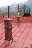 Old brick chimney on black tile roof (mountain background) Stock Photography