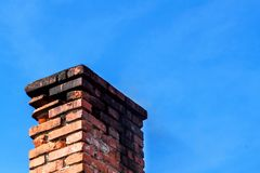 Old brick chimney. Chimney with sky in the background. Eco-friendly heating of a family house. Old brick chimney. Chimney with sky in the background. Eco Stock Images