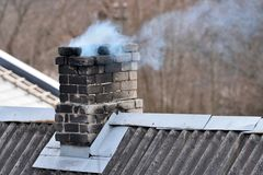 Old brick chimney. On old house roof stock photography