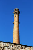 Old brick chimney, industrial archeology. A detailed view of an old brick chimney, with a stone wall, against a bright blue sky, chemical industry, from palermo Stock Images