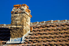 Old brick chimney and roof. Top with bright sky background Royalty Free Stock Photos