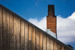The old brick chimney on the roof Stock Photo