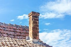 Old brick chimney on the roof top from house with blue sky stock photography
