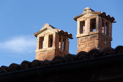 Old brick chimneys. Two brick chimneys on tile roof against clear blue sky Stock Photo