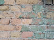 Old brick city wall, pink bricks and sprinkled plaster of the tender green color, modern background texture, free space for text. Royalty Free Stock Photos