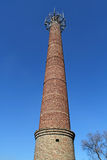 Old brick factory chimney high against the bright blue sky. Royalty Free Stock Image