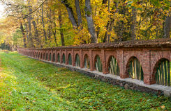 Old brick fence in autumn landscape Stock Photography