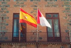 Old brick governmental building on the street of Toledo old town. City center with two spanish flags at the balcony on sunny day Stock Images