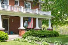 Old brick home with flag. Old brick house with American flag on front porch Stock Photos