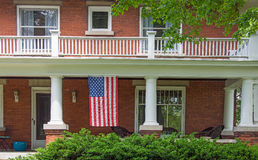 Old brick house with American flag. American flag hanging on front porch old brick house Stock Photo