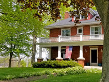 Old brick house with American flag. On porch Stock Photos