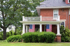 Old brick house with hanging American flags Stock Photography