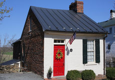 Old brick house with a red door. An old brick house with a white wall and a red door Royalty Free Stock Photo