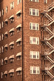 Old brick housing complex in downtown Wichita, Kansas. Rows of windows and old metal fire escape stairway crisscrossing down the outside of a brick apartment Royalty Free Stock Images