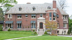 Old Brick Mansion. Massive, old red brick mansion with awnings Stock Images