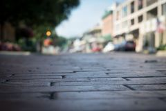 Old brick pavers on Front Street in Natchitoches. And background bokeh Royalty Free Stock Images