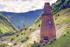Old brick pipe on the ruins of a small factory in the mountains stock image