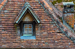 Old brick roof with window and a chimney Royalty Free Stock Image