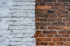 Old brick urban wall half painted white Royalty Free Stock Photography