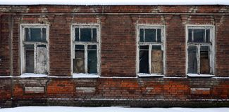 An old brick wall of an apartment house with a lot of boarded up windows without glass.  royalty free stock photography