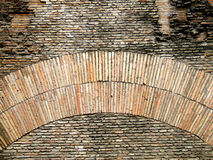 Old brick wall and arch. Interesting shapes on an old brick wall with an arch. Rome architecture Stock Photography