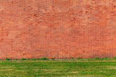 Old brick wall background. Large red brick wall background and grass stock photography