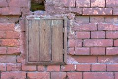Old brick wall with a closed wooden window. royalty free stock photography