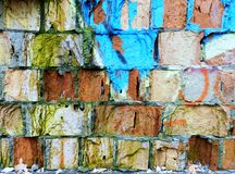 Old brick wall with colorful graffiti Stock Photos