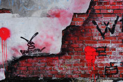 Old Brick Wall with crumbling Plaster. And paintings Stock Image