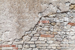 Old brick wall with damaged concrete stucco layer. Flat background photo texture Royalty Free Stock Image