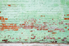 Old brick wall with damaged layer of green paint. Background photo texture Stock Photos
