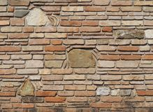 Old brick wall with embedded stones of different sizes and fragments of terracotta roof tiles in the texture.  Stock Image