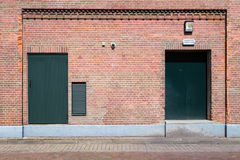 Old brick wall with green doors and street Stock Photography