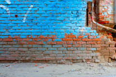 Old brick wall half painted in bright blue color Royalty Free Stock Image