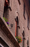 Old brick wall with lantern and flower decoration, detail in downtown of Ferrara, Italy Stock Photos